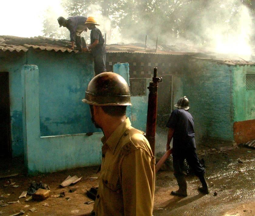 Ugunsdzēsējs cenšas nodzēst liesmas Ahmadabadā Dudhešver reģionā.