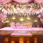 Līgava un līgavainis sēž viesu zālē uz īpaši viņiem dekorētas skatuves